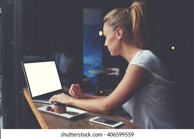 Young female student working on net-book with blank copy space screen for your text message or promotional content, cute woman successful freelancer using laptop computer while sitting in coffee shop