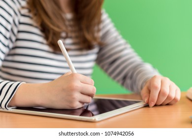 Young female student writing notes using digital tablet during class. Generation Z Education concept.