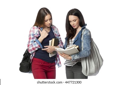 Young female students standing with books and bags, isolated on white