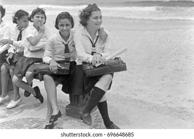 Young female students in uniforms sitting on beach