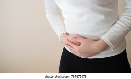 Young female suffering form abdominal pain on gray background w/ copy space. Causes of abdominal pain include dysmenorrhea, endometriosis, PMS or ovarian cyst. Gynecology and health care concept.