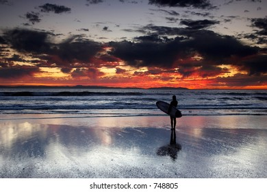Young female with a surfboard watching a colorful sunset.