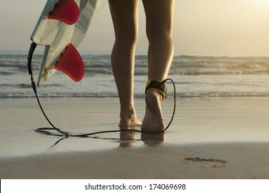 Young female surfer girl feet surfboard early morning surf
