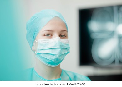 young female surgeon on a background of a monitor with a tomography of the brain.