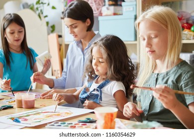 Young female and sweet girls sitting at table in art school and painting bright pictures together