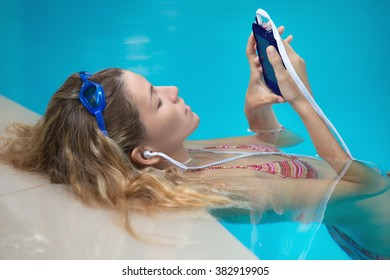 Young female swimer is listening to music