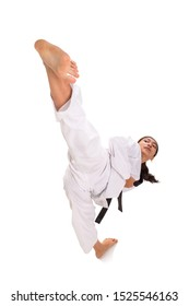 Young female taekwondo master showing her high kick technique, full length shot isolated over white background