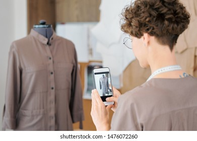 Young female tailor with smartphone photographing jacket model on mannequin