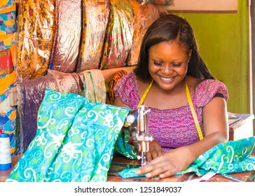 young female tailor smiling while sewing clothes with her sewing machine