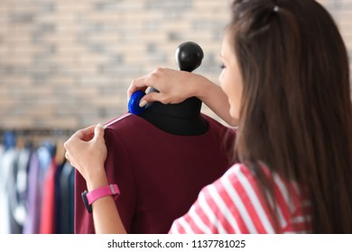 Young female tailor taking measurements of dress on mannequin in atelier