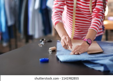 Young female tailor working with sewing pattern in atelier