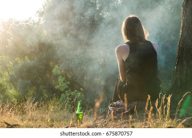 Young female takes rest outdoors at camping place in the forest. Woman sits under a tree and enjoys sunset near the forest with bottle of cold drink