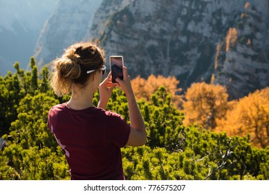 Young female is taking a photo of autumn colors in the mountains with her mobile phone in Triglav National Park in Slovenia.