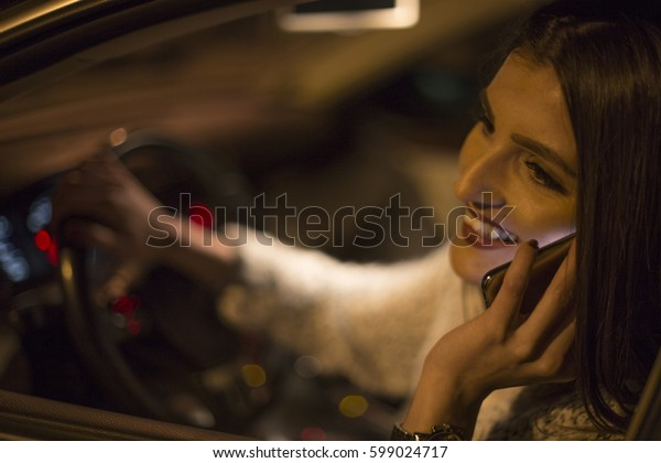 Young female talking on a phone and smiling while driving a car in night