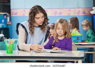 Young female teacher and girl reading book with children in background at preschool