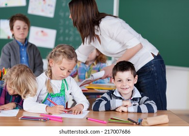 Young female teacher in kindergarten class with a group of diverse young students leaning over to direct a young boy at the back of the classroom