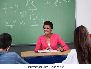 Young female teacher looking away while sitting at desk with students in foreground