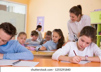 Young female teacher and pupils working in classroom at elementary school
