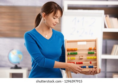 Young female teacher teaching mathematics in elementary school classroom, holding abacus, looking down, smiling.