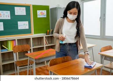 Young female teacher using an alcohol spray to disinfect student desks in classroom. Asian woman in face mask cleaning the tables with antiseptic sanitizer. School reopen after quarantine and lockdown