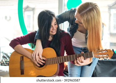 Young female teaching her girlfriend to play guitar.