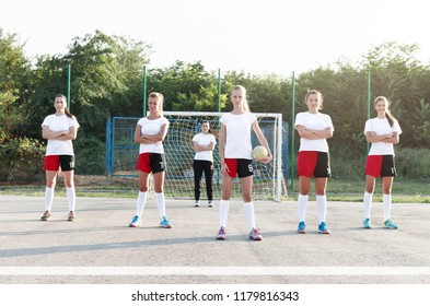 Young female team players of handball, standing on court and looking at camera.