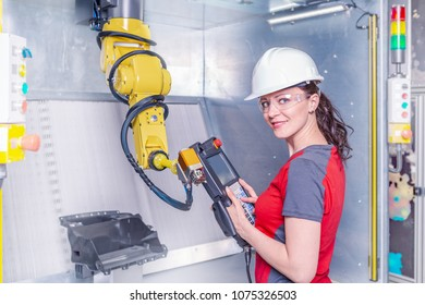 A young female technician while machine constructing in a manufacturing plant