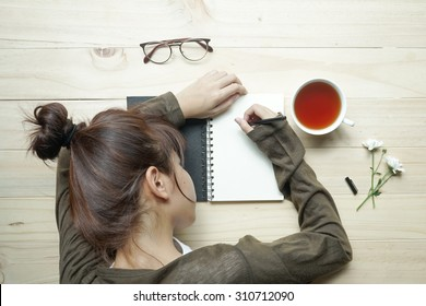 young female teenager writing or drawing on notebook with cup of tea and white flowers on wooden table. Top view