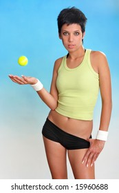 Young female with tennis ball on cyan-blue background