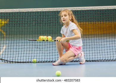 young female tennis player on tennis court holding balls on racket in gym