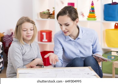 Young female therapist and little girl during play therapy session