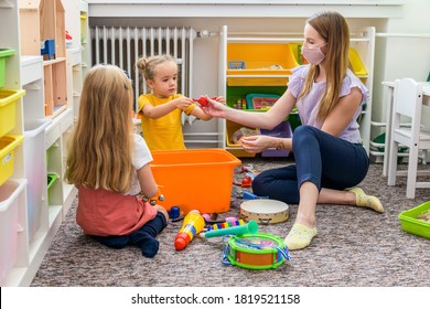 Young female therapist wearing protective face mask playing with two toddler girls during occupational child therapy.