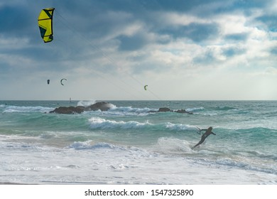 A young female at the time of kitesurfing near the stormy sea under the white clouds
