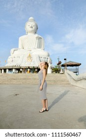 Young female touris standing near concrete statue of Buddha in Phuket. Concept of tourism in Thailand and landmarks.