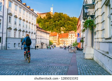 Young female tourist with backpack riding a bicycle in the old city center of Ljubljana in Slovenia