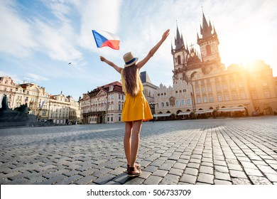Young female tourist dressed in yellow holding czech flag on the old town square of Prague. Enjoying great vacation in Czech republic