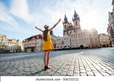Young female tourist dressed in yellow standing with raised hands on the old town square of Prague. Enjoying great vacation in Czech republic