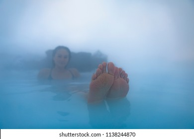 Young female tourist enjoying Blue Lagoon Geothermal Spa in Iceland