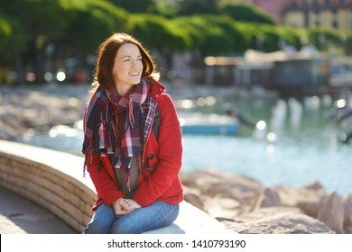 Young female tourist enjoying the view of small yachts and fishing boats in marina of Lerici town, located in the province of La Spezia in Liguria, Italy. Traveling off season.