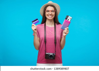 Young female tourist holding credit card and passport with tickets, ready to flight, isolated on blue background