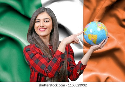 Young female Tourist holding Earth Globe against flag of Ireland