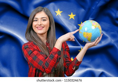 Young female Tourist holding Earth Globe against flag of European Union