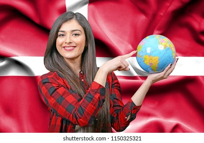 Young female Tourist holding Earth Globe against flag of Denmark