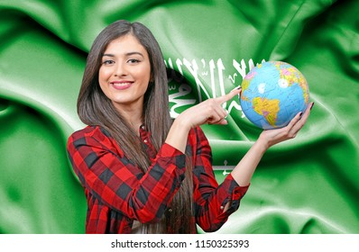 Young female Tourist holding Earth Globe against flag of Saudi Arabia