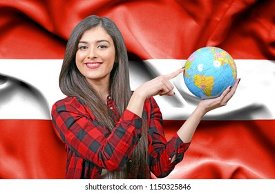 Young female Tourist holding Earth Globe against flag of Austria