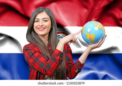 Young female Tourist holding Earth Globe against flag of Paraguay