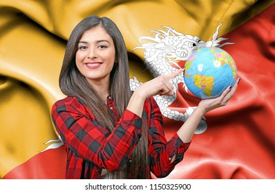 Young female Tourist holding Earth Globe against flag of Bhutan
