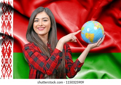 Young female Tourist holding Earth Globe against flag of Belarus