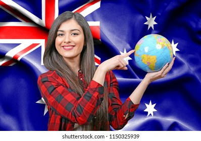 Young female Tourist holding Earth Globe against flag of Australia