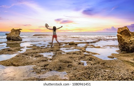 Young female tourist jumps in ecstasy at Neil Island rocky beach at sunset. Photograph shot at Natural bridge Neil island Andaman India.
